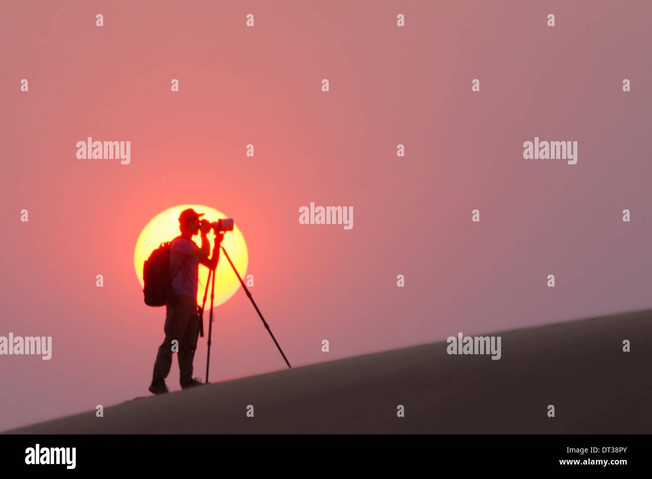 Fotografen, die Silhouette in der untergehenden Sonne in der Namib-Wüste, Namibia Stockbild