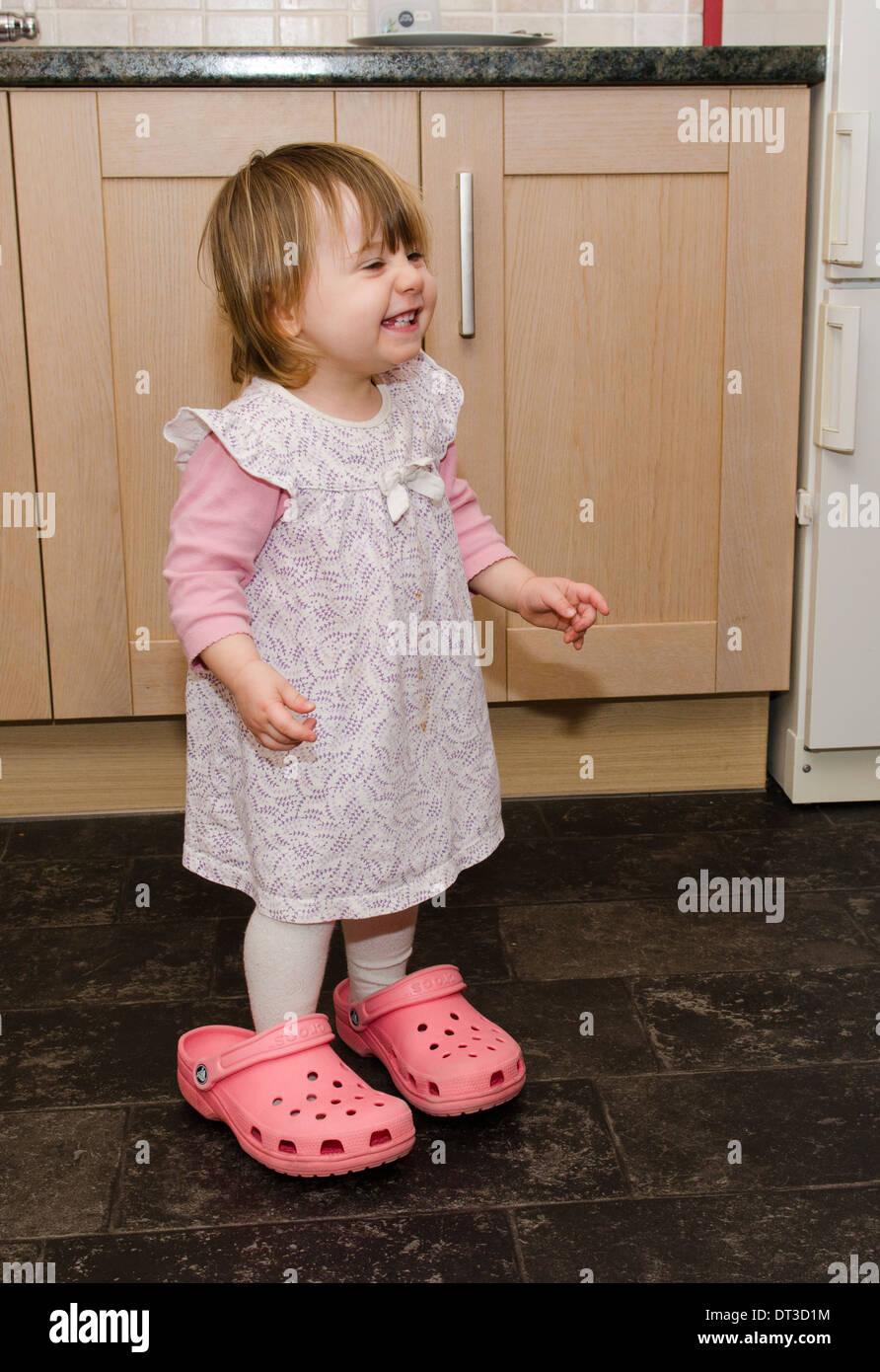 18 Monate altes Mädchen Mutter Crocks Schuhe tragen. Stockfoto