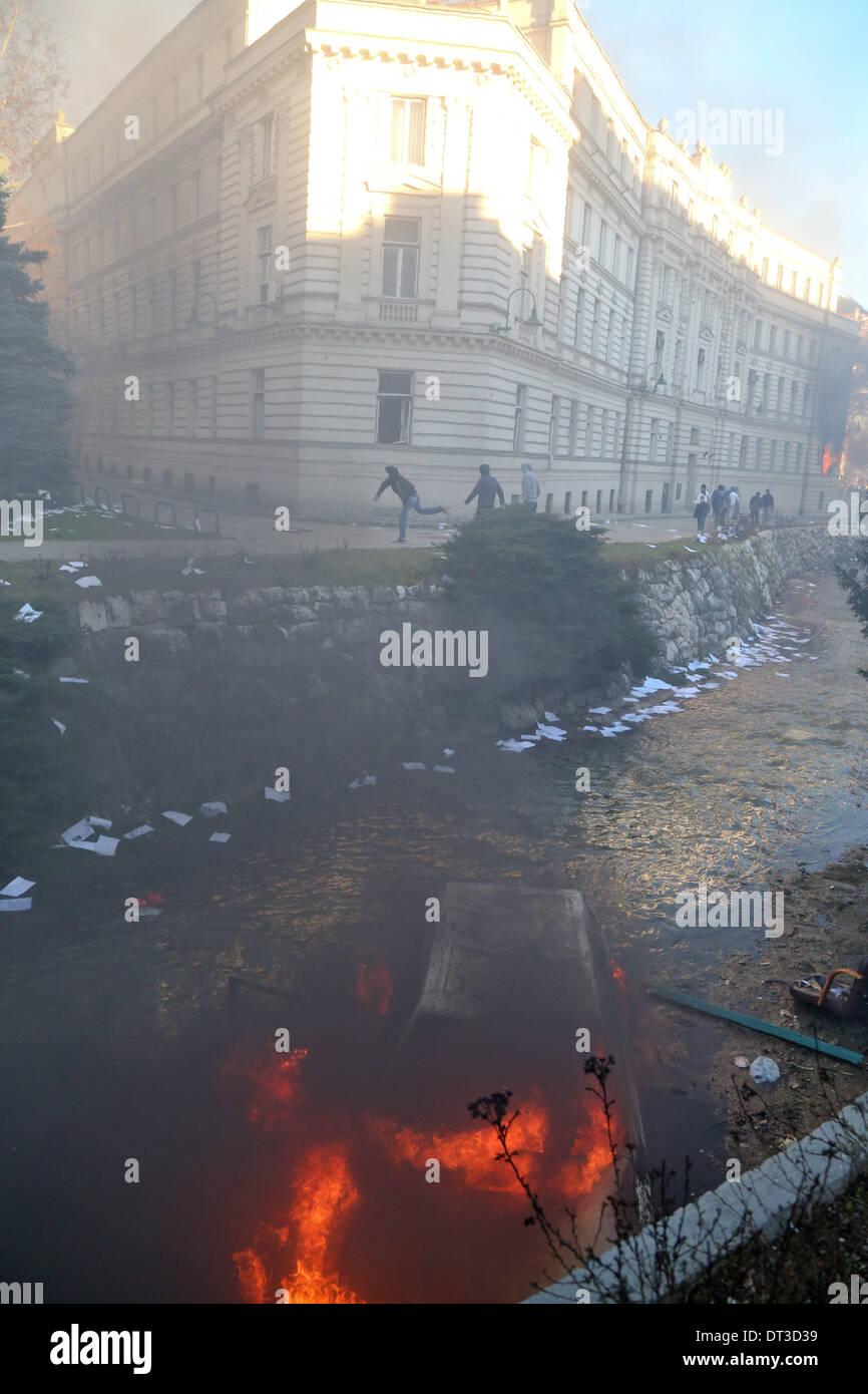 Sarajevo, Bosnien und Herzegowina. 7. Februar 2014. Ein verbranntes Auto ist zu sehen in einem Fluss in der Nähe der Regierung Gebäude des Kantons Sarajevo gestürzt, wie Demonstranten mit der Polizei rund um das Gebäude in Sarajevo, die Hauptstadt von Bosnien und Herzegowina, am 7. Februar 2014 kollidieren. Mehr als 2.000 Demonstranten hier stießen mit der Polizei gewaltsam am Freitag, Brandstiftung auf die Presidential Gebäude und Regierung Gebäude des Kantons Sarajevo. Bildnachweis: Haris Memija/Xinhua/Alamy Live-Nachrichten Stockbild