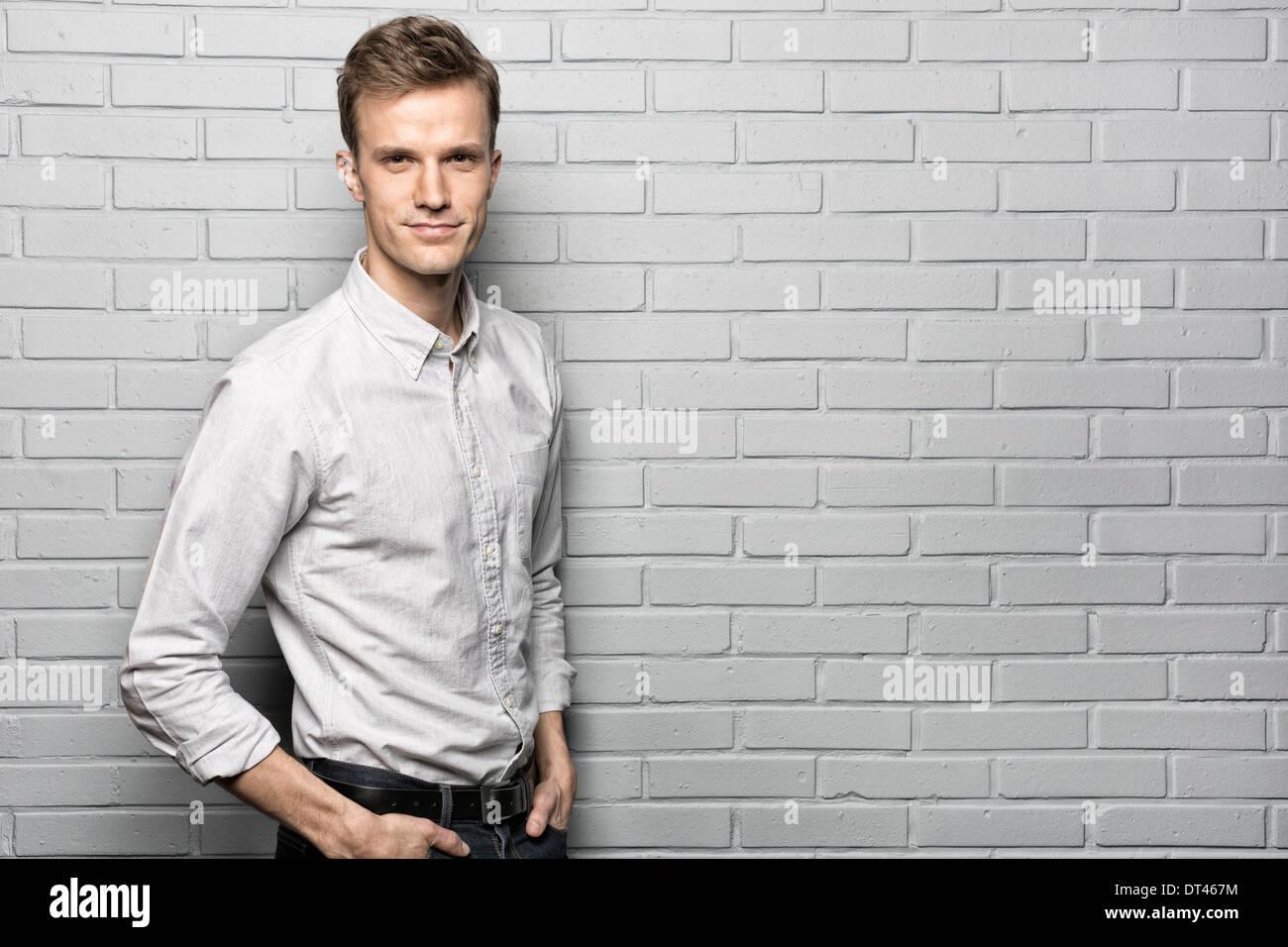 Männlichen casual Porträt Lächeln Studio Ziegel Kamera suchen Stockbild