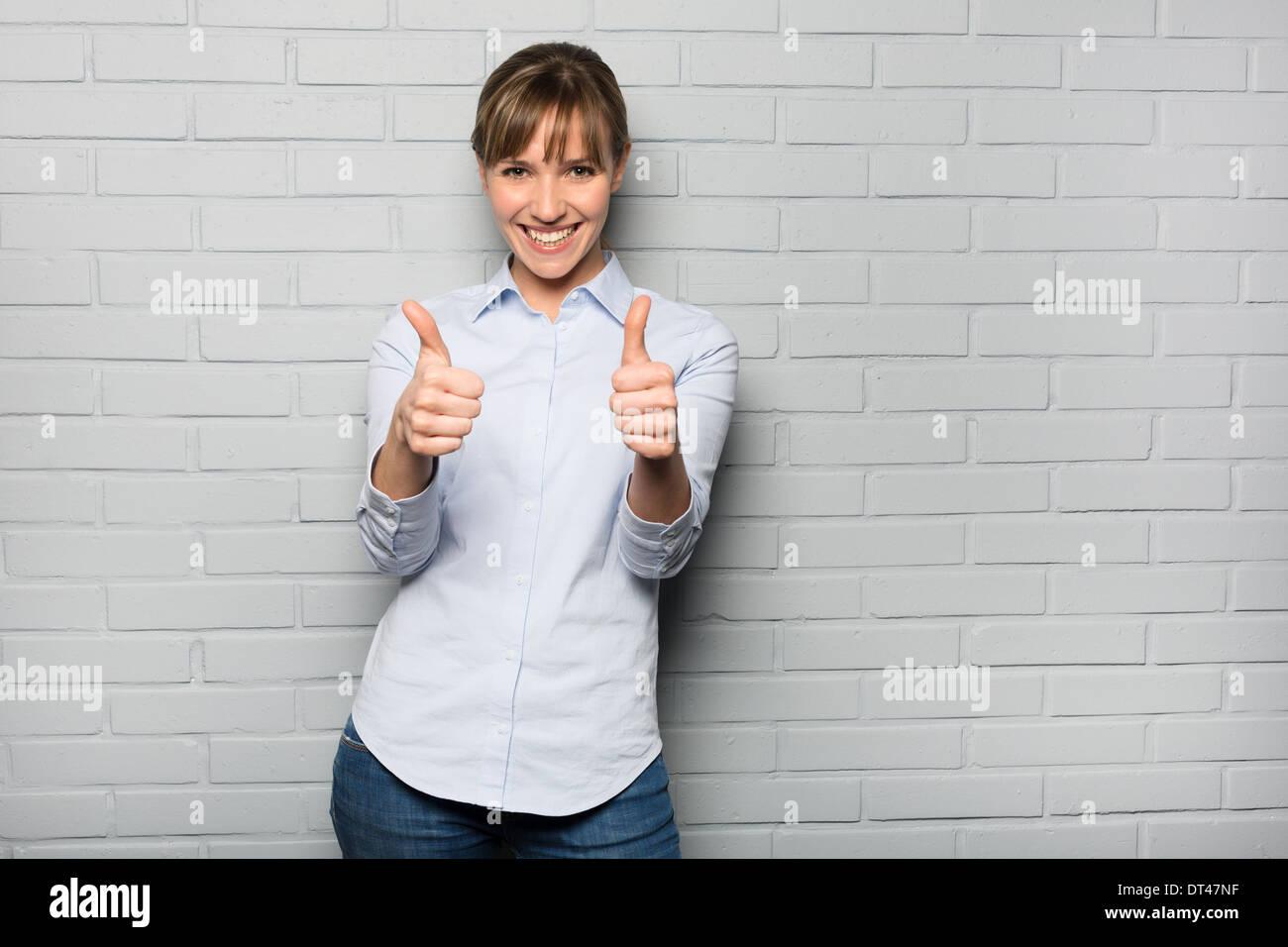 Weibliche casual fröhlich Studio Geste grauen Hintergrund Stockbild