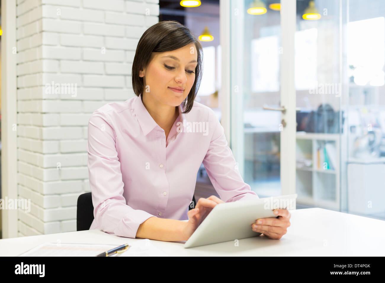 Brünette Frau mit Tablet Computer am Schreibtisch im Büro Stockbild