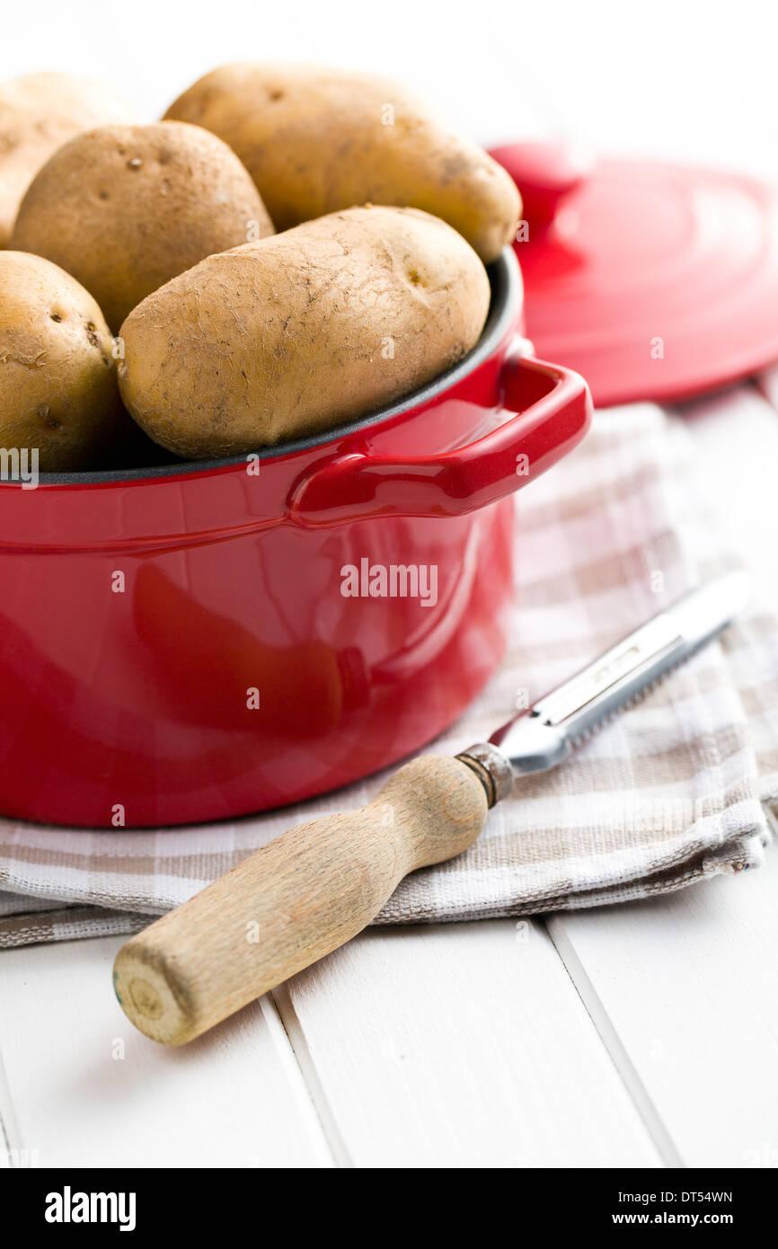 die rohen Kartoffeln und alten hölzernen Schäler Stockbild