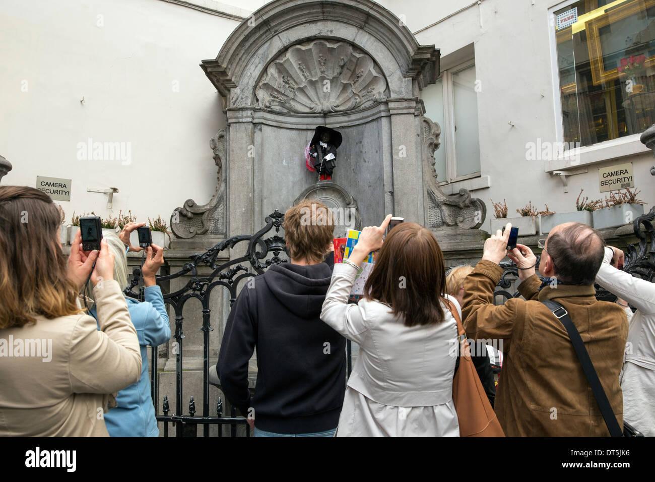 Touristen fotografieren der Statue Manneken Pis in Brüssel Stockbild