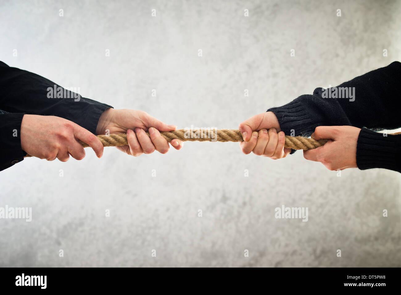 weibliche Hände Zugseil auf gegenüberliegenden Seiten. Rivalität Konzept. Stockbild
