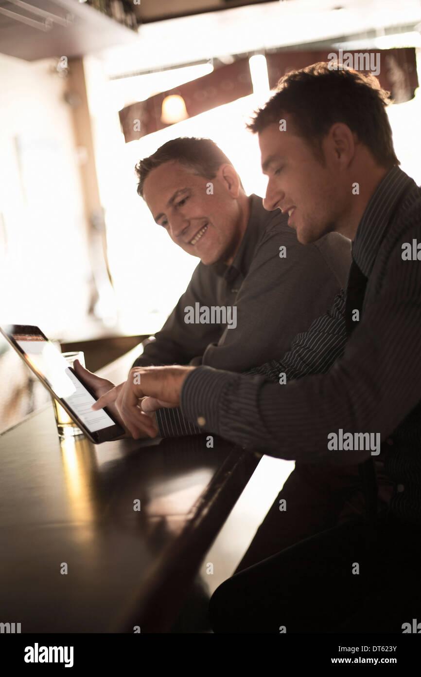 Zwei Geschäftsleute, die auf der Suche bei Digital an der bar Stockbild