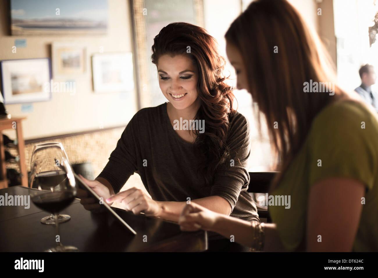Geschäftsfrauen Blick auf digital-Tablette in der Weinbar Stockbild