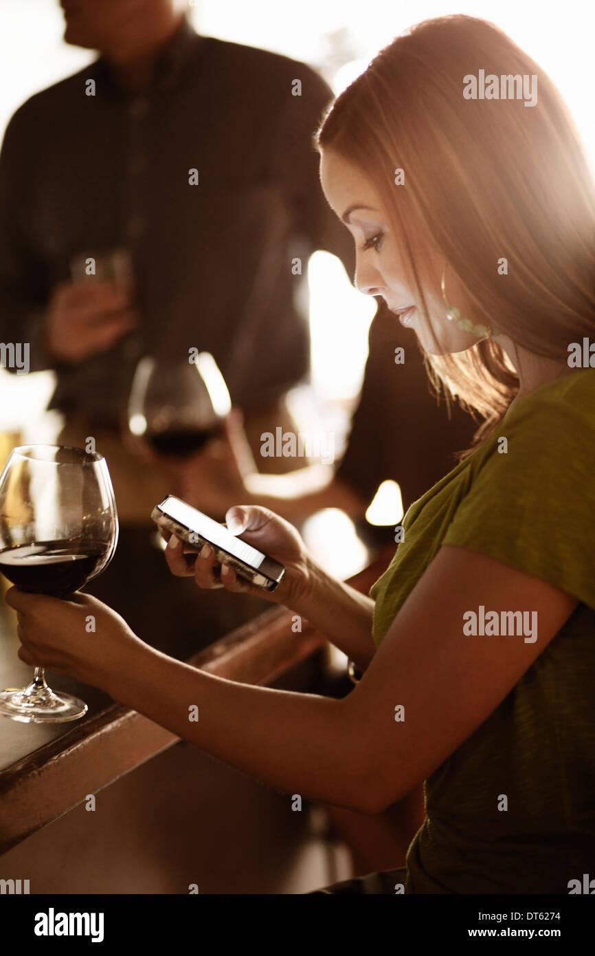 Geschäftsfrau Blick auf Handy in der Weinbar Stockbild