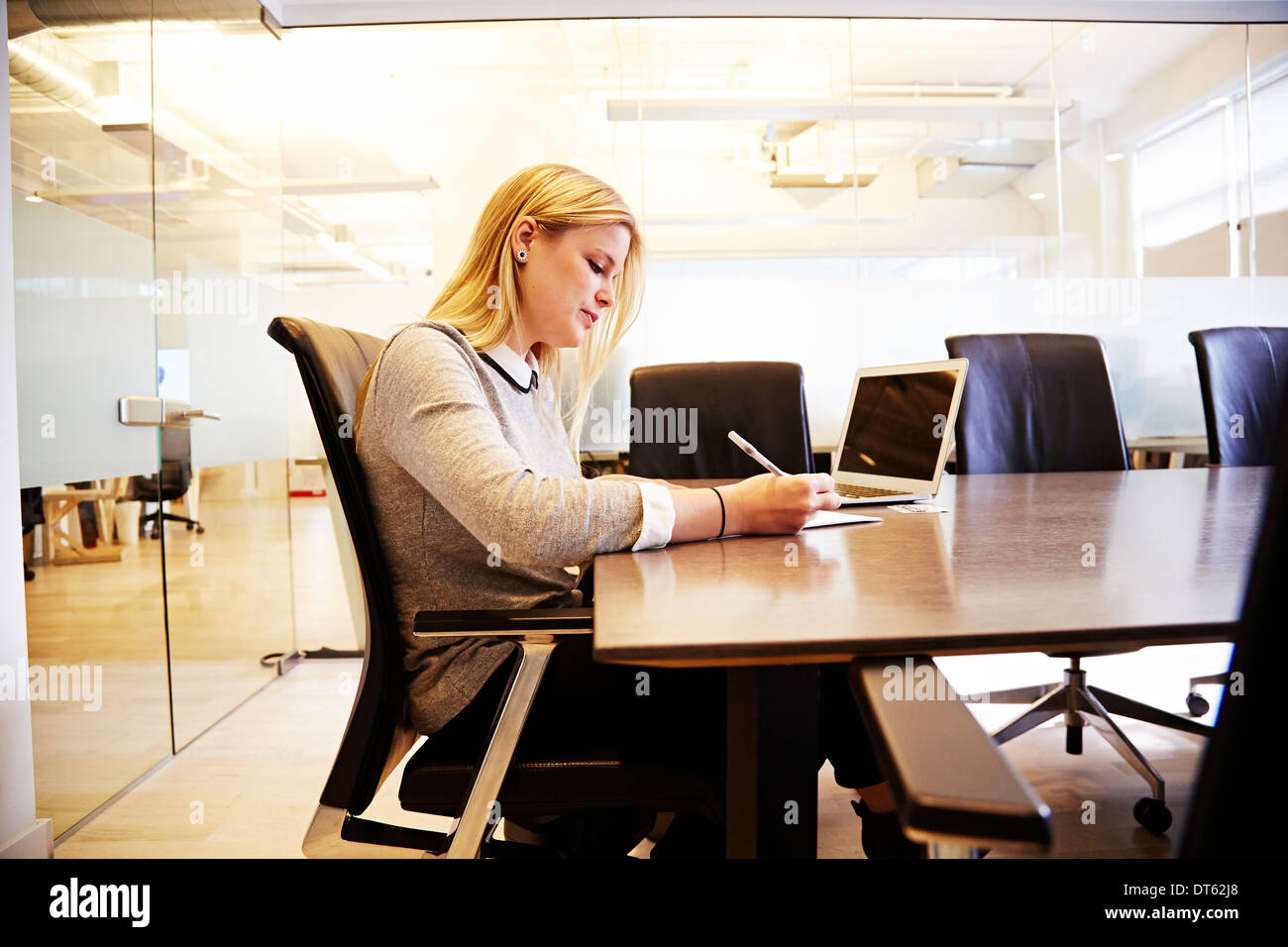 Junge Frau am Tisch arbeiten Stockbild