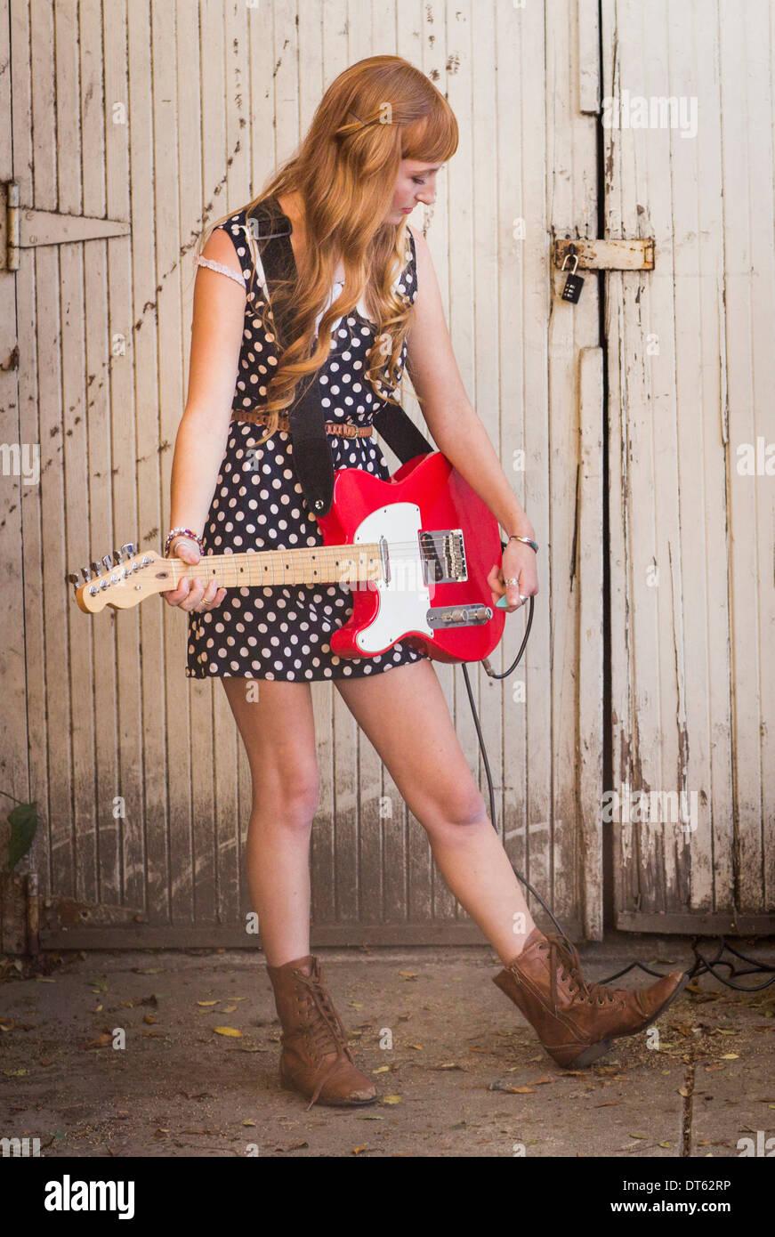 Junge Frau spielt e-Gitarre in Hof Stockbild