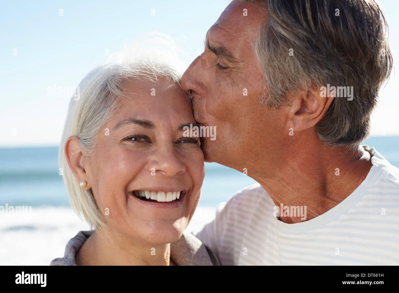 Mann küssen Frau auf Stirn Stockfoto