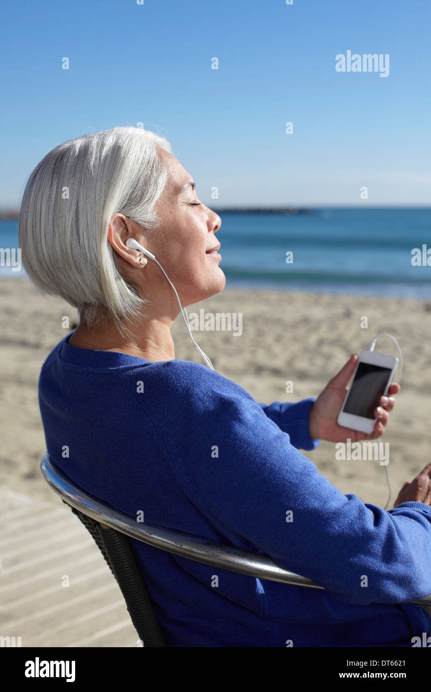 Reife Frau Musikhören mit Kopfhörer am Strand Stockbild