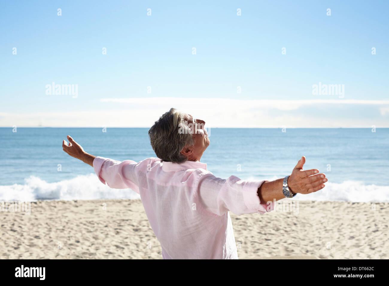 Ältere Mann mit ausgebreiteten Armen am Strand Stockbild