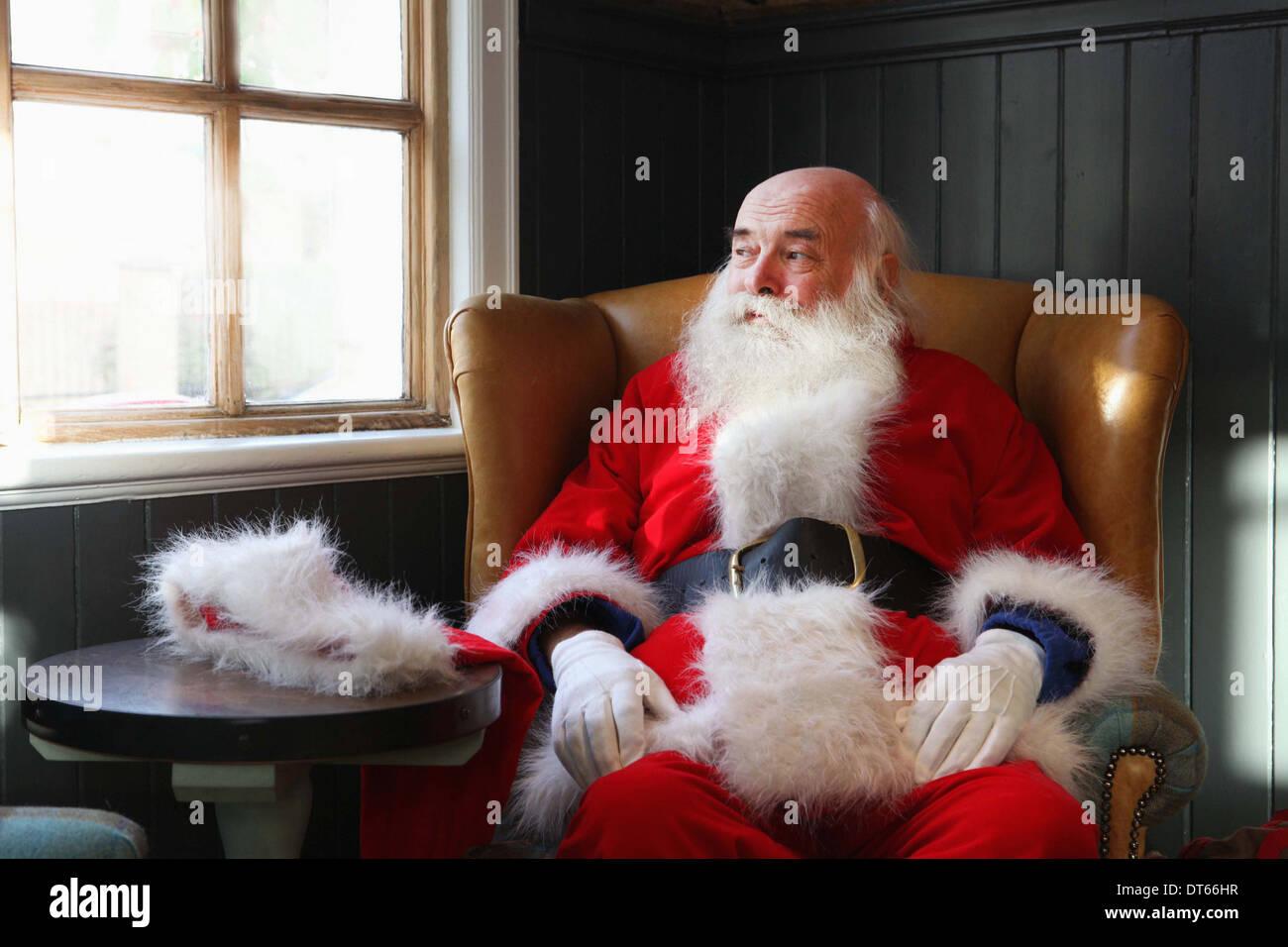 Santa Claus Einnahme Pause im Sessel Stockbild