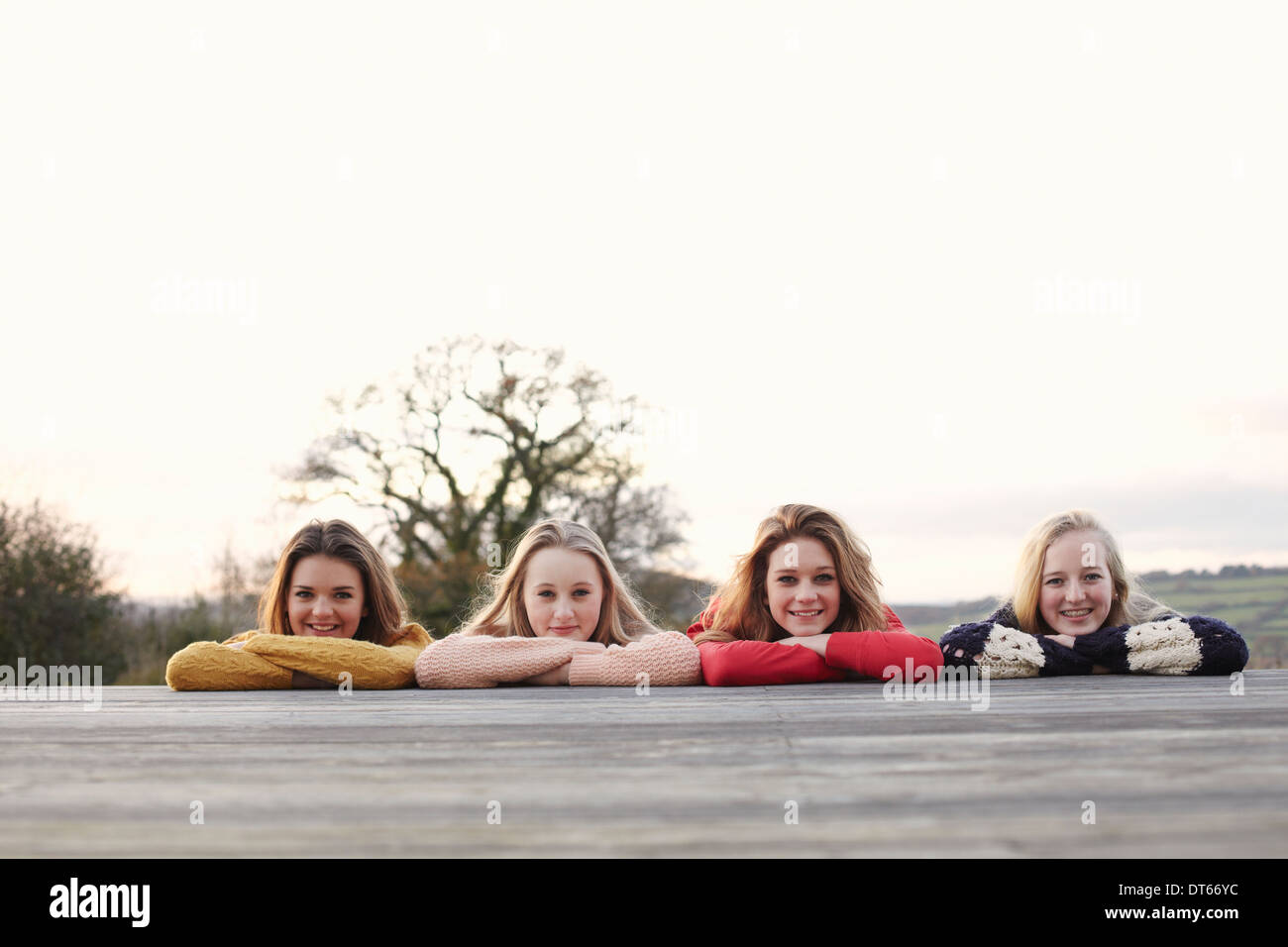 Vier Mädchen im Teenageralter in einer Reihe auf Terrasse Stockfoto
