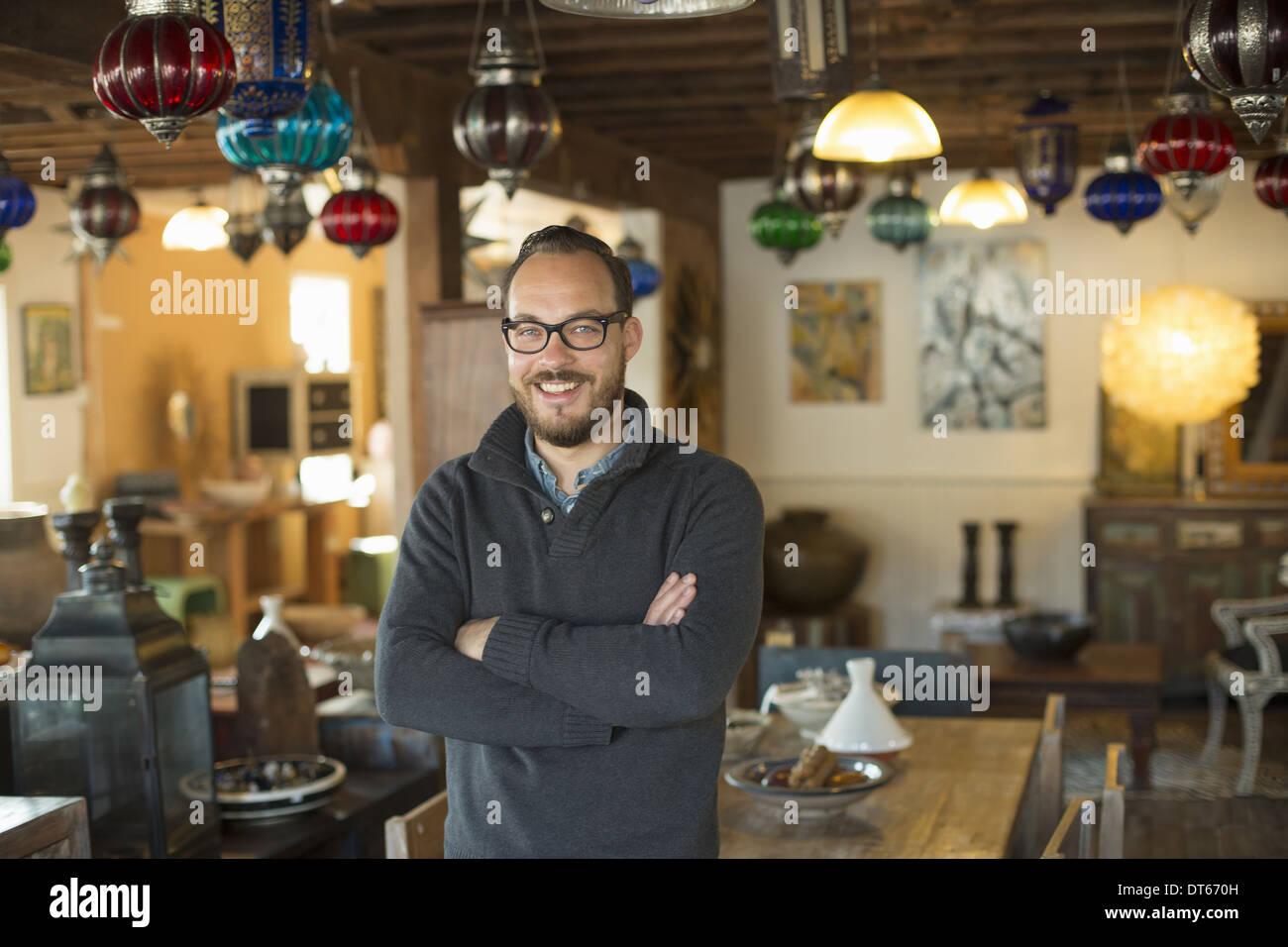 Ein Mann steht in einem Laden voller Antiquitäten und dekorative Objekte. Antiquitätengeschäft zeigt. Beleuchtung, Opalglas und Möbel. Stockbild