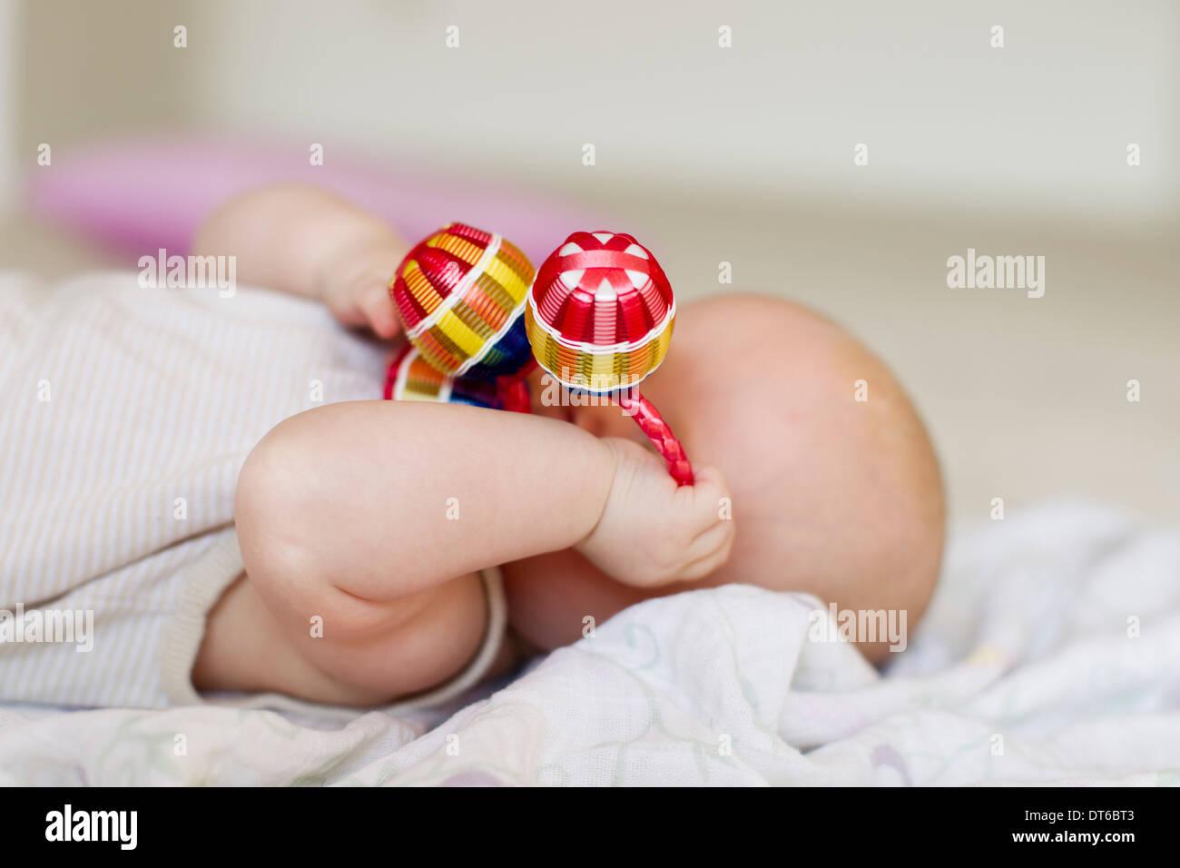 Babymädchen liegend mit Rassel für Gesicht Stockbild