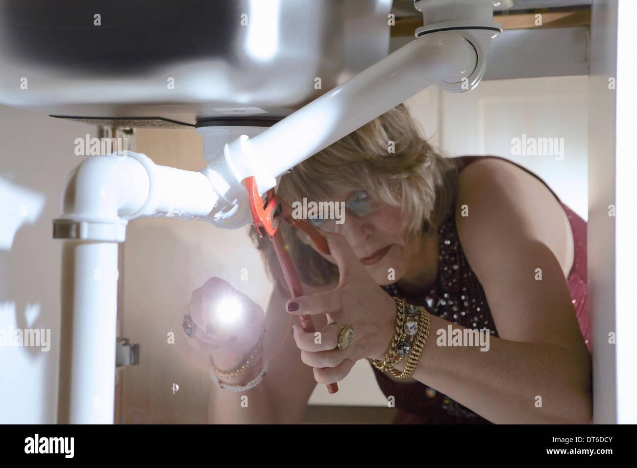 Ältere Frau in Abendgarderobe, die Fixierung der Rohre unter Küchenspüle Stockbild