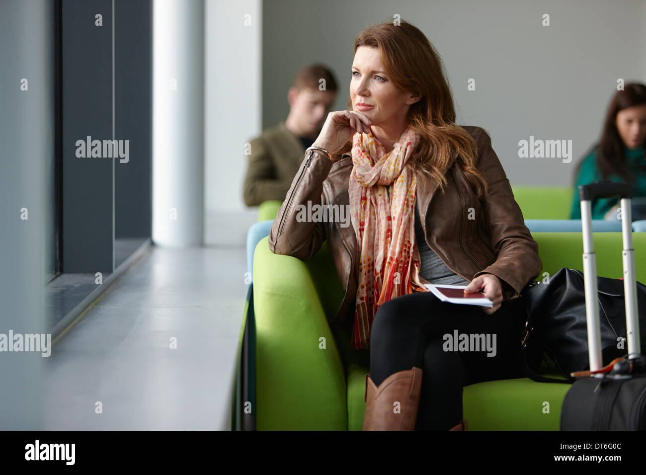 Reife Frau in Abflughalle Stockbild