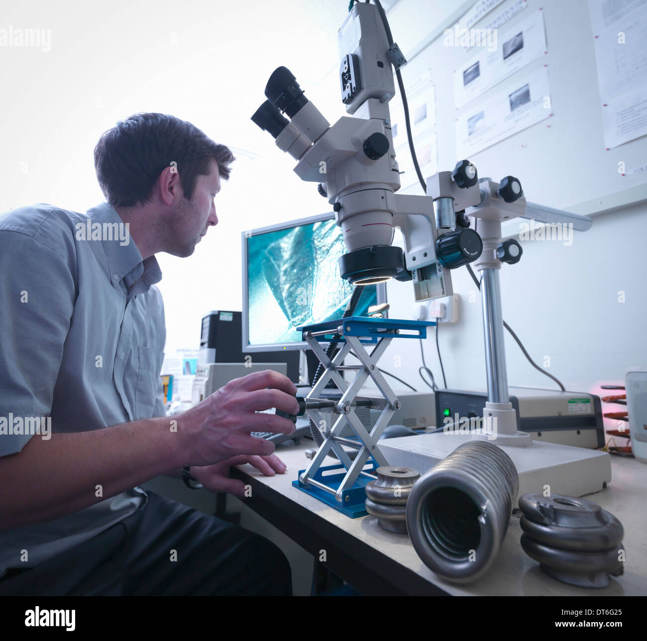 Wissenschaftler mit Mikroskop, um Schäden zu überprüfen, bis zum Frühjahr Stockbild