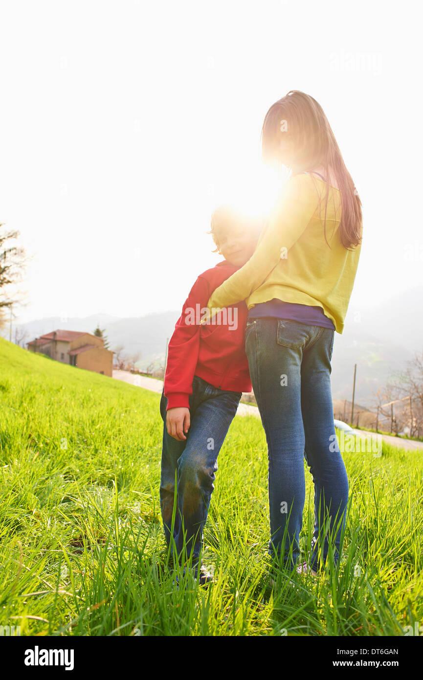 Junge und ältere Schwester auf Wiese Stockfoto