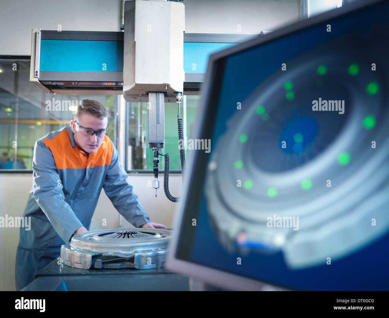 Arbeiter mit Messgerät in Fabrik Stockbild