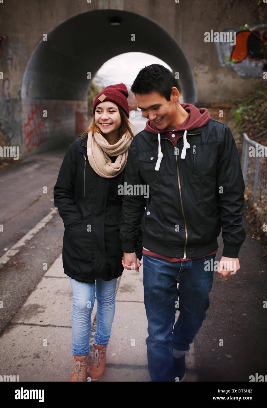 Junges Liebespaar zu Fuß auf einer Straße Lächeln auf den Lippen. Gemischte Rassen paar zu Fuß auf dem Bürgersteig. Stockbild