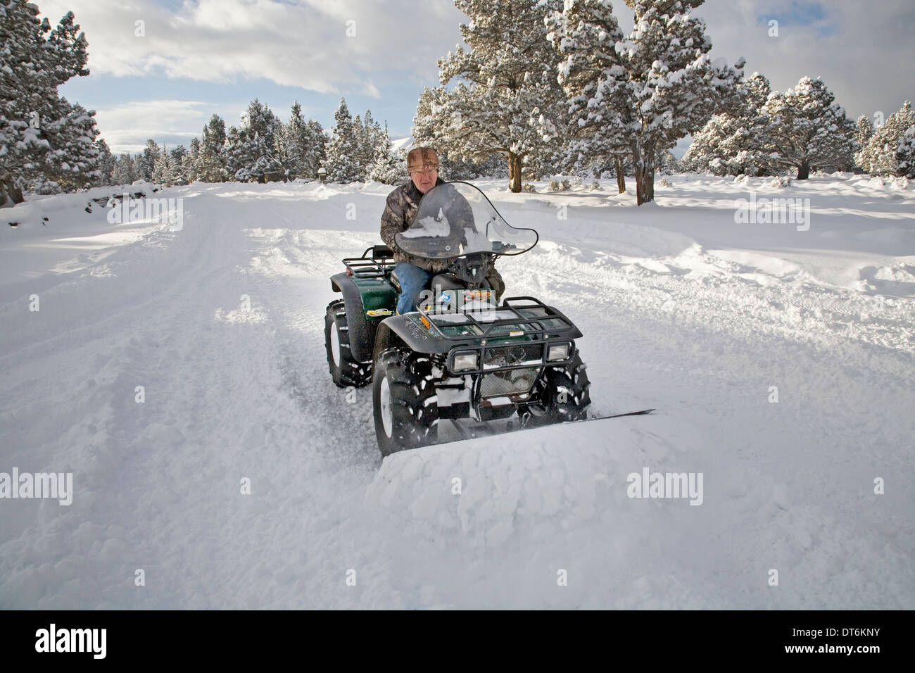 Eine Seniorin Pflüge Schnee mit einem ATV, all-Terrain-Fahrzeug, nach einem großen Schneesturm in Zentral-Oregon. Stockbild