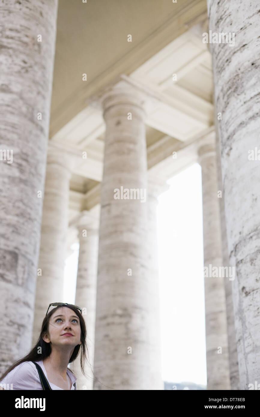 Eine Frau betrachtet die hohen Säulen und Bögen eines historischen Gebäudes in Rom. Stockbild