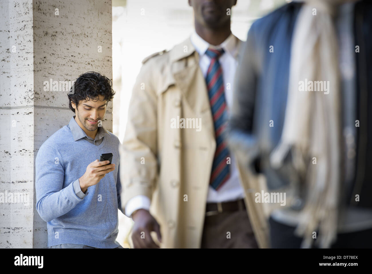 Drei Menschen auf dem Bürgersteig, ein Mann mit seinem Handy, ein Mann im Regenmantel und ein junger Mann auf der Straße. Stockbild