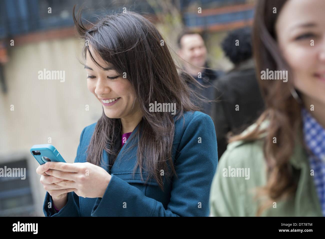 Eine Frau, die Überprüfung ihrer türkisfarbenen Smartphone unter anderen Leuten auf einer Stadtstraße. Stockbild
