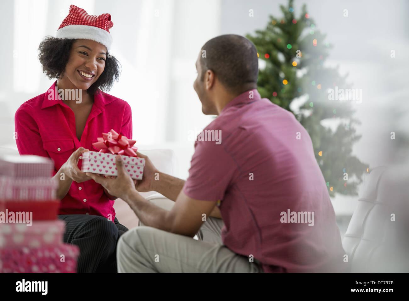 Eine Frau trägt einen roten und weißen Weihnachtsmann Hut.  Zuhause. Ein geschmückter Weihnachtsbaum. Stockbild