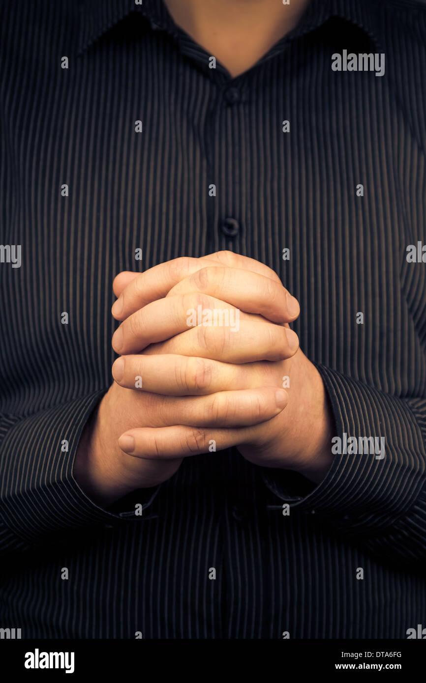 Ein Mann trägt ein Shirt mit gefalteten Händen Stockbild