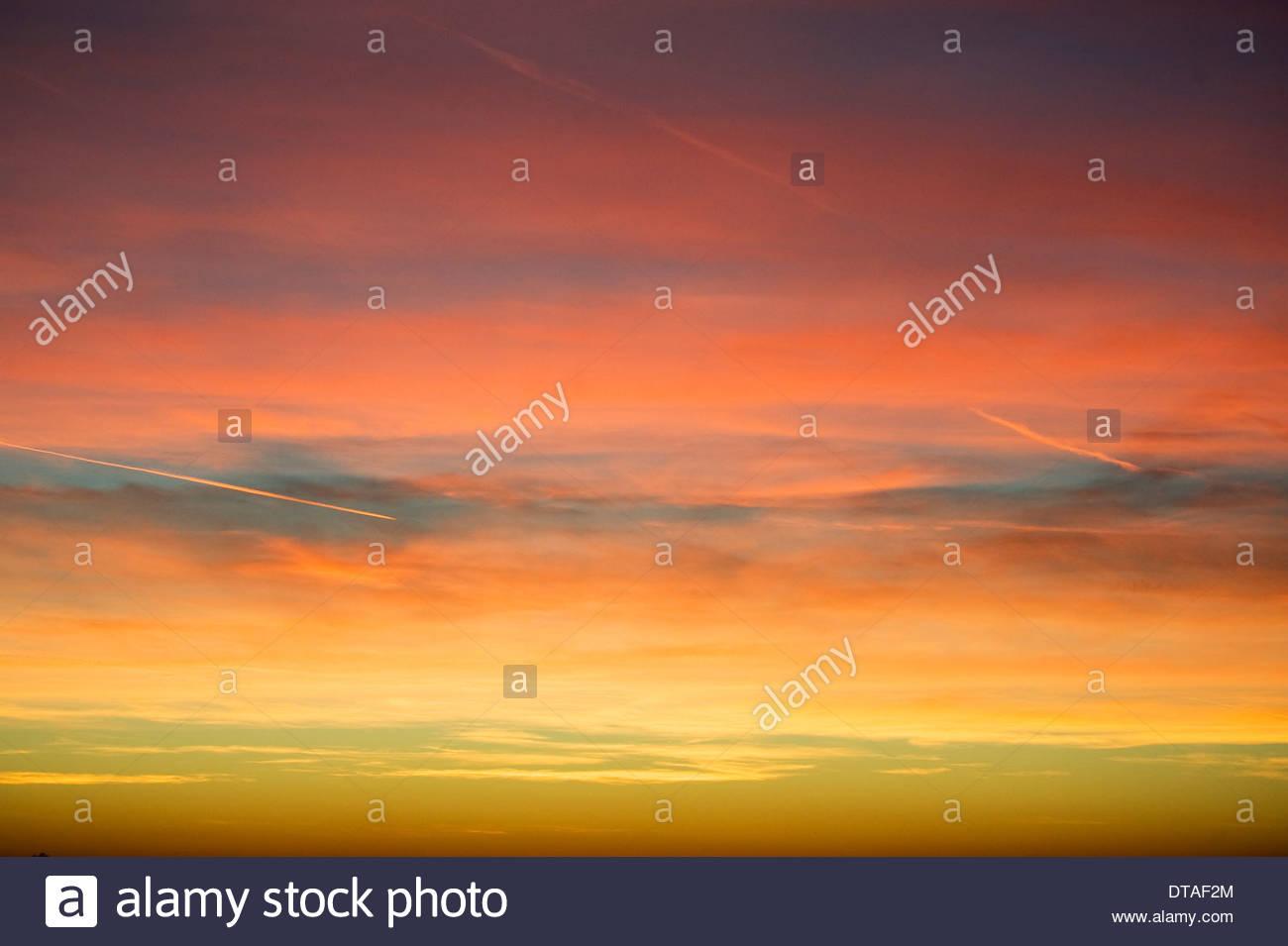 trübe Wolke Wolkengebilde Himmel bei Sonnenuntergang mit vielen Farben Graduierung Dampf Kondensstreifen Stockbild