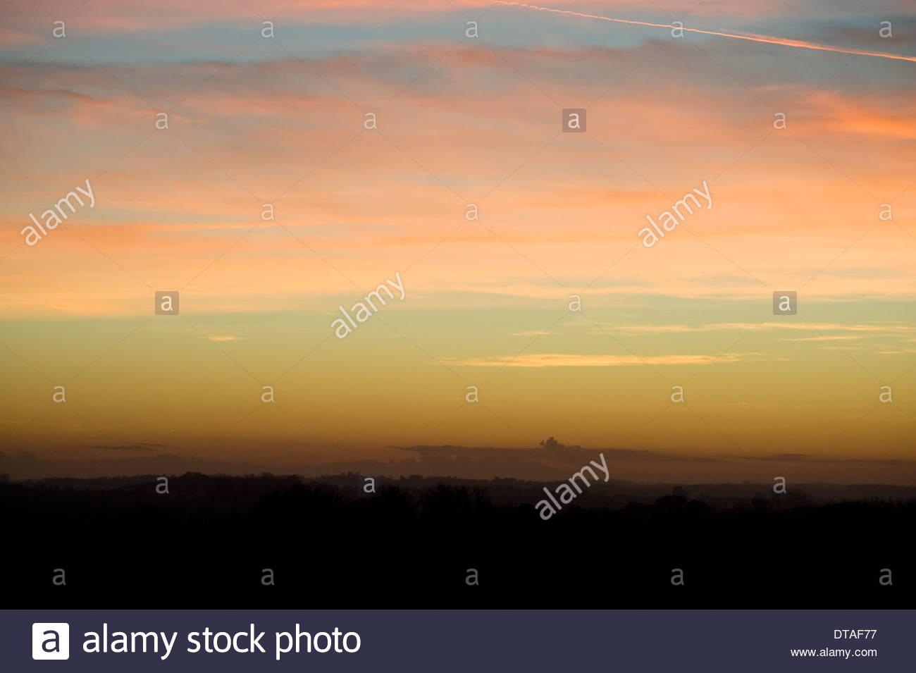 trübe Wolke Wolkengebilde Himmel bei Sonnenuntergang mit vielen Farben Graduierung Kondensstreifen Stockbild