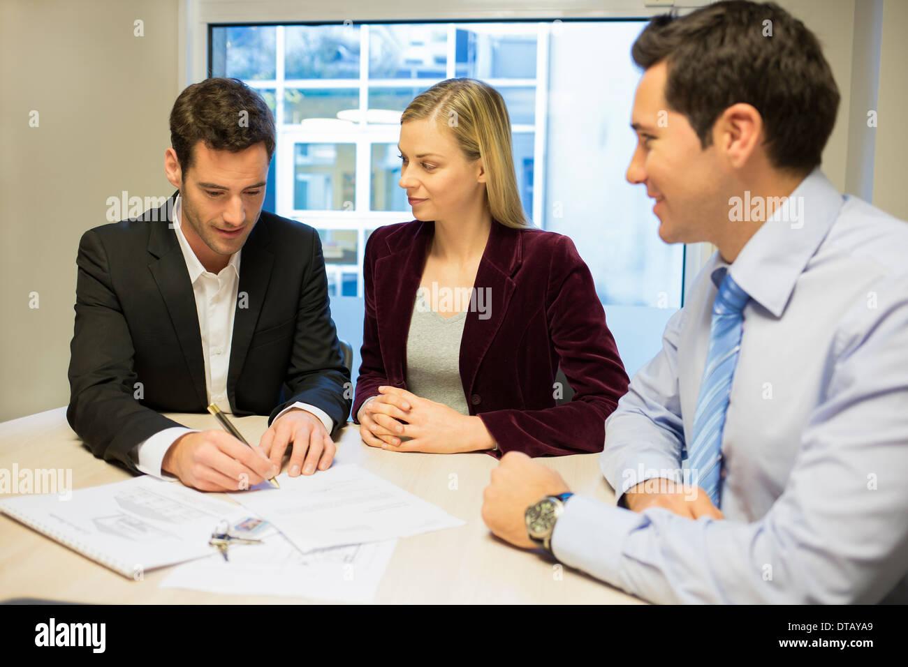 Junges Paar Vertragsunterzeichnung im Büro mit Immobilien, neue Eigentümer Stockbild