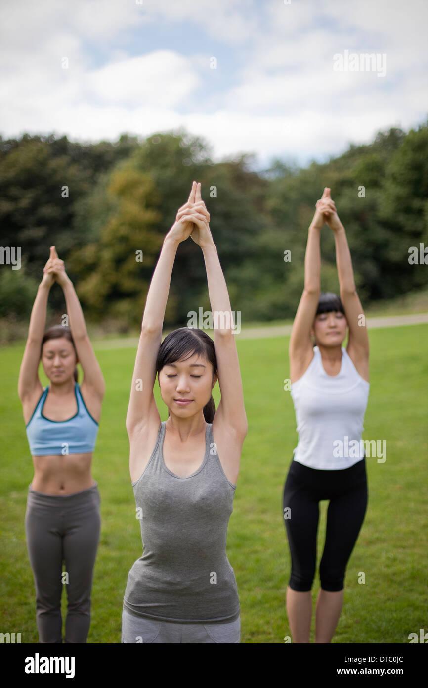 Drei junge Frauen im Park üben Yogaposition Stockbild