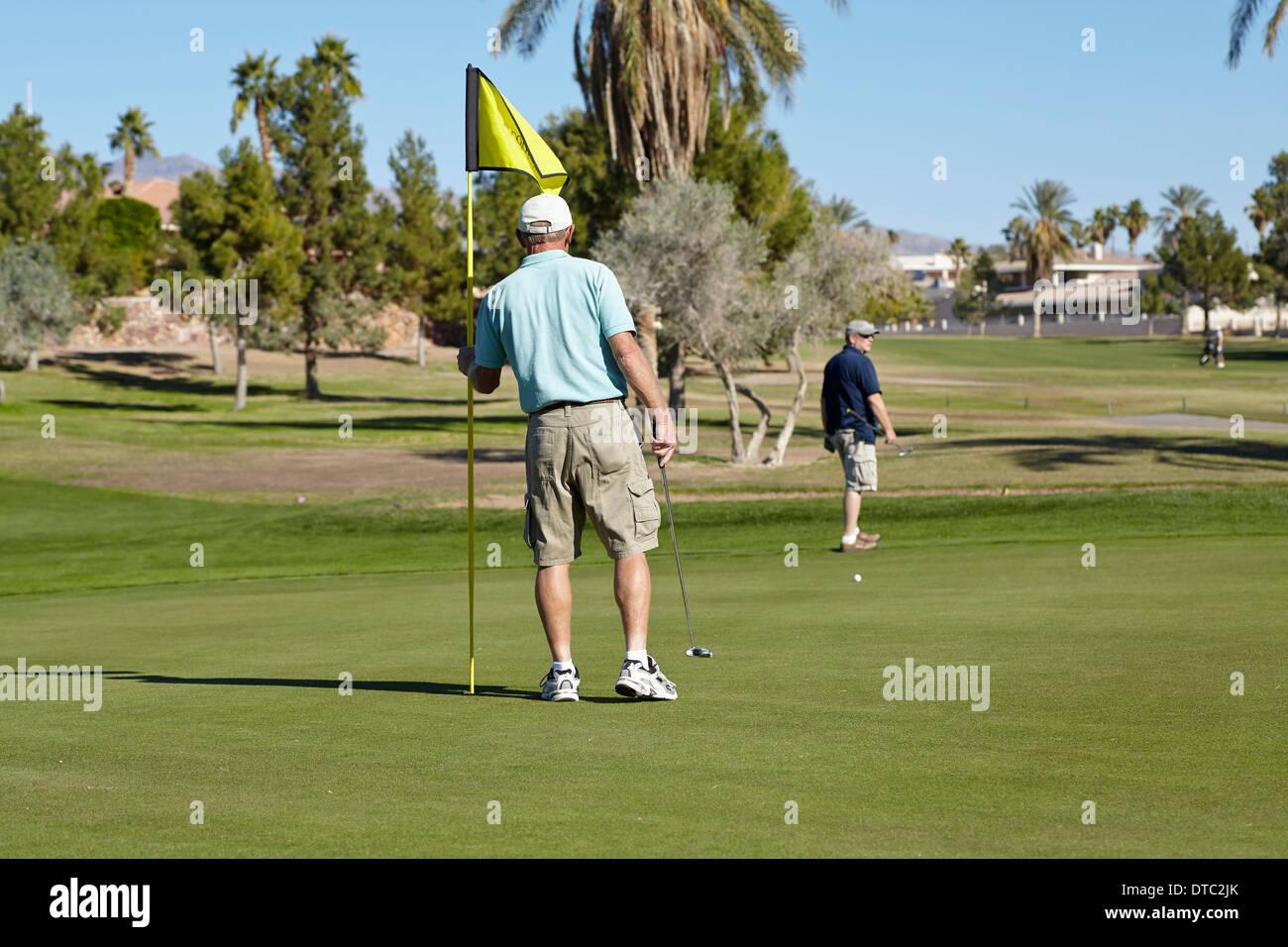 Zwei männliche Golfer auf dem Grün mit Fahne Stockbild