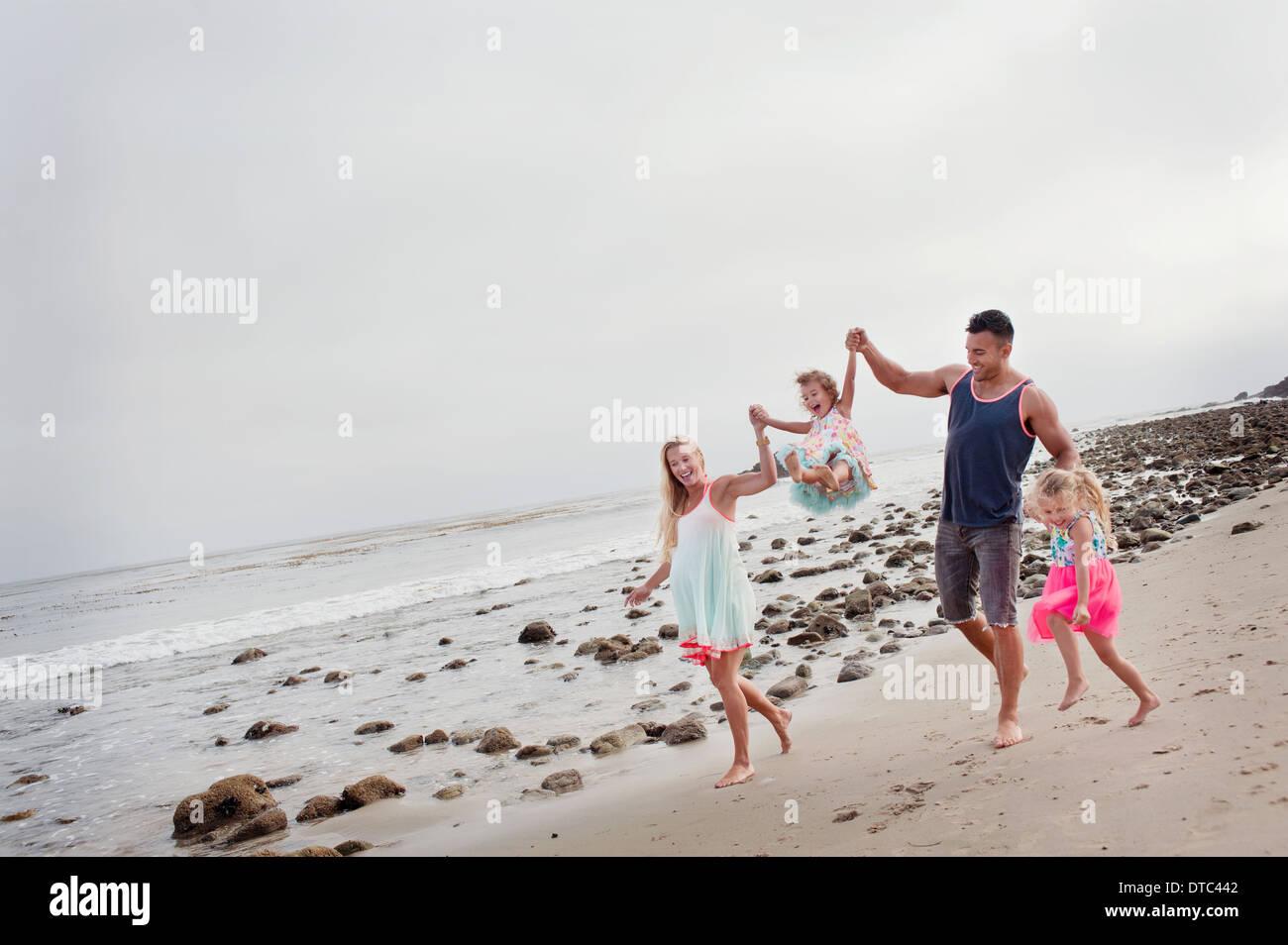 Eltern und zwei junge Mädchen zu Fuß am Strand Stockbild