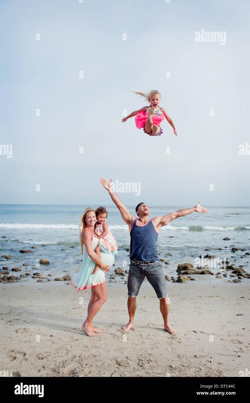 Eltern und zwei junge Mädchen am Strand herumalbern Stockbild