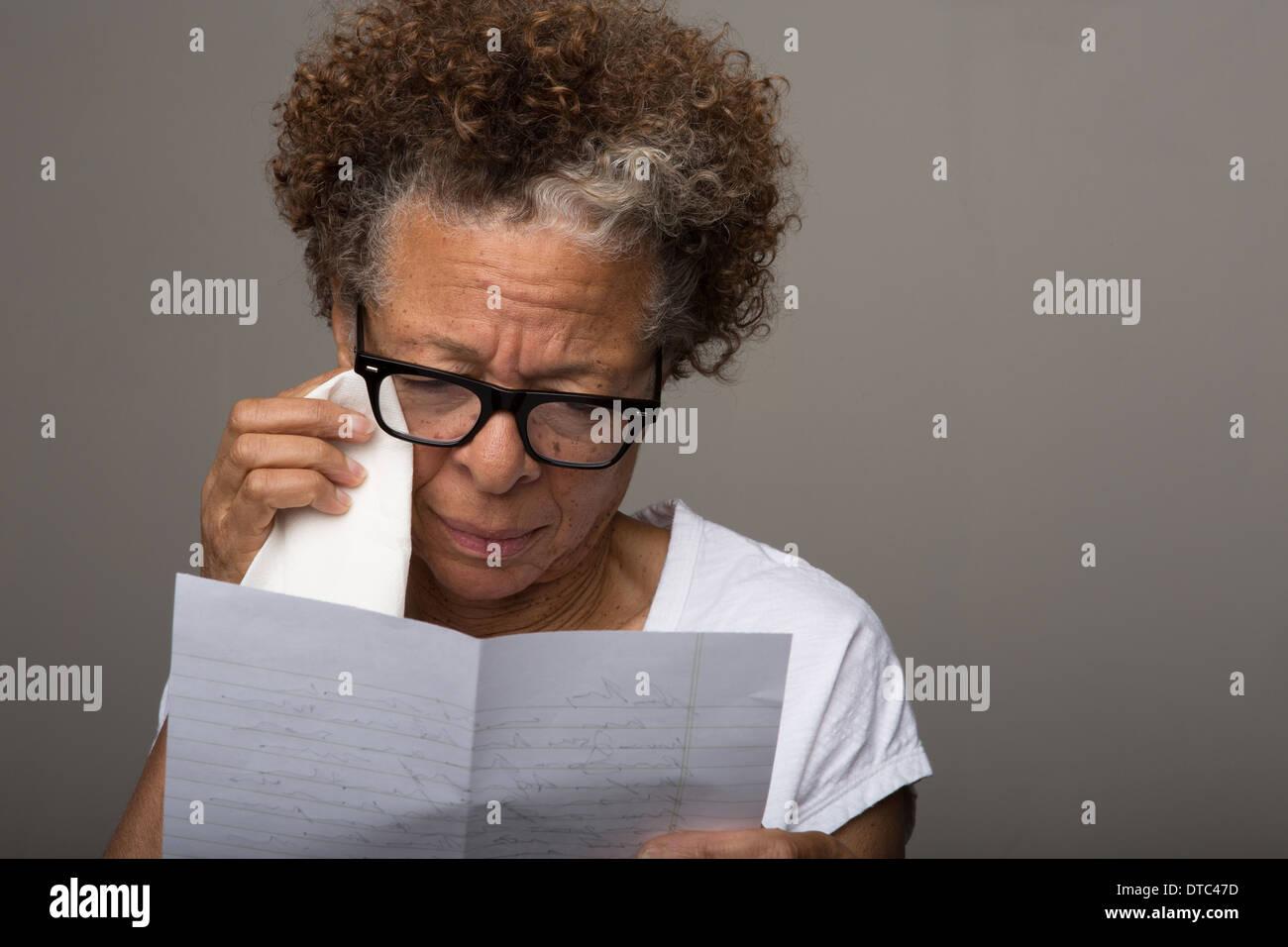 Studioportrait traurig senior Frau liest einen Brief Stockbild