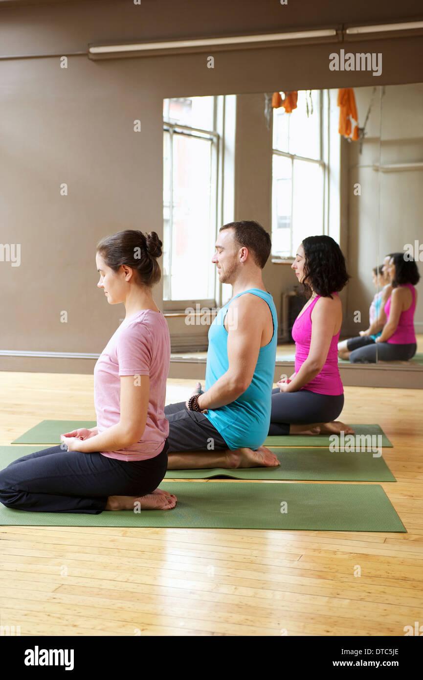 Menschen, die kniend im Yoga-Kurs Stockbild