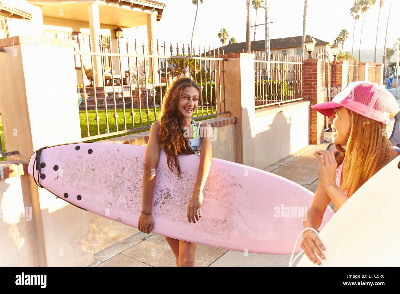 Zwei Mädchen tragen Surfbretter Lachen und Lächeln Stockbild