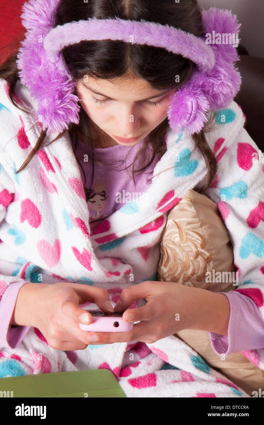 Teenager-Mädchen im Chat online auf ihrem Mobiltelefon Stockbild