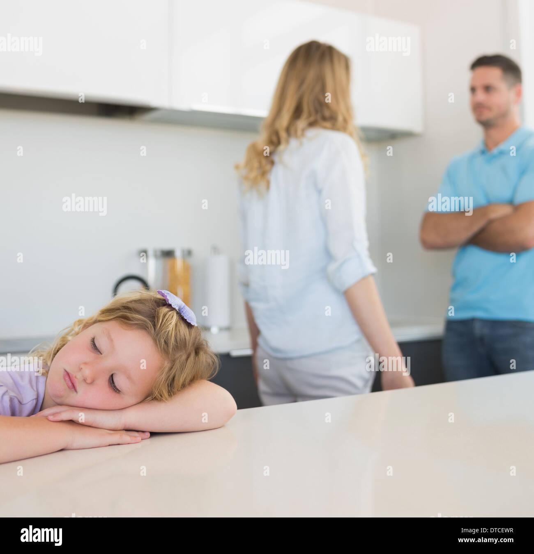 Mädchen am Tisch, während Eltern streiten Stockbild