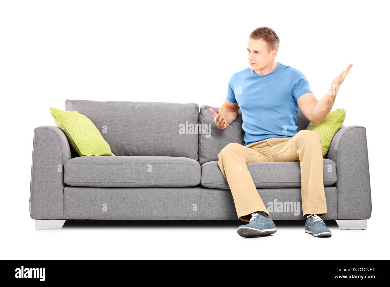 Verärgerter Mann auf der Couch sitzen und seine Hand heftig schwingen Stockbild