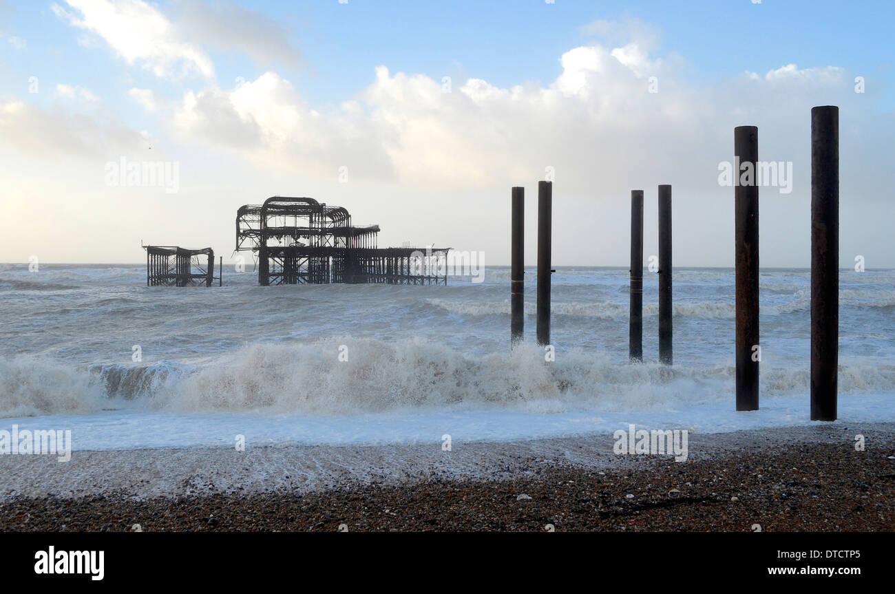 Brighton hove seafront Promenade Promenade winter storm Kieselsteine Geländer Strandhütten Sitzbank Bänke Wellen über Weg Stockbild