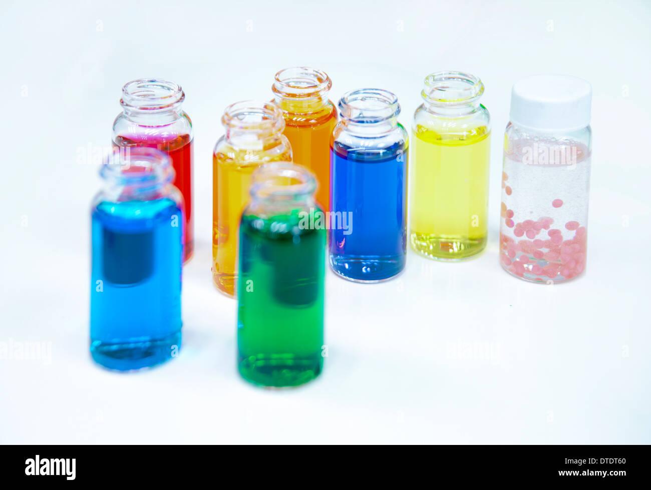 Glasflaschen mit farbigen Flüssigkeit bei einem Kosmetikhersteller Stockbild