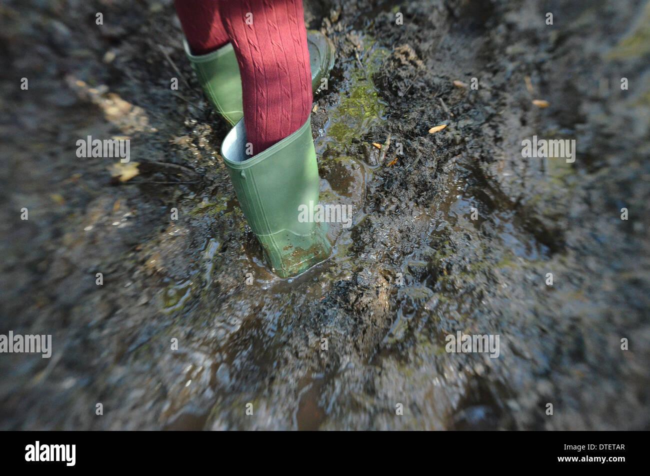 Des Mädchens Füße in grüne Gummistiefel Schlamm zu spielen. Stockbild