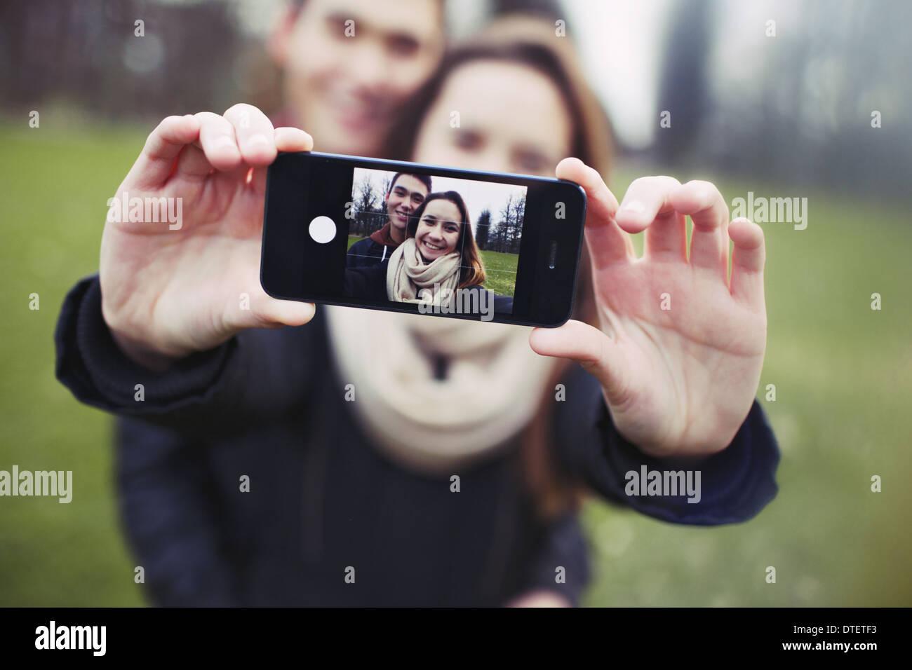 Zärtlich junges Paar unter einem Selbstporträt mit einem Smartphone im Park. Gemischte Rassen Teenager Mann und Frau im Freien. Stockbild